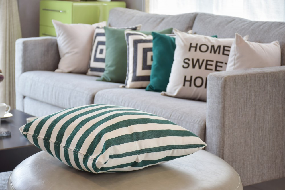 green striped pillows on the cozy grey sofa in the living room