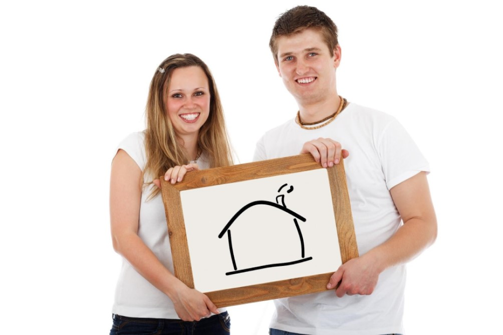 couple holding a house drawing